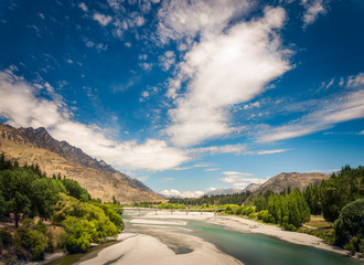 View of  Shotover river and Bridge, with the Remarkables mountain in the background, Queenstown, New Zealand. Shotover river was formerly one of the richest gold bearing rivers in the world.