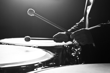 Hands musician playing the timpani closeup in black and white
