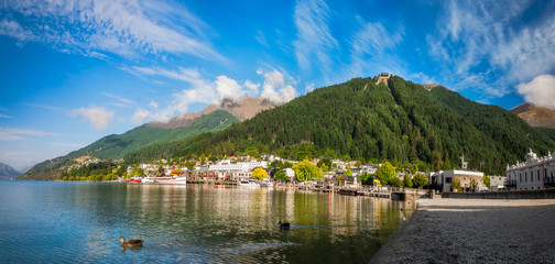 View of the alpine city of Queenstown in New Zealand, from the marina bay of Lake Wakatipu with the Queenstown Skyline mountain in the background.