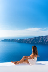 Wall Mural - Luxury travel vacation Europe tourist woman relaxing at fancy hotel resort balcony in greek Santorini island, Greece with view over the Mediterranean Sea and Oia. Elegant girl living jetset lifestyle.