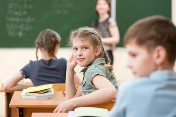 Happy schoolchildren sitting at desk, classroom