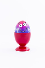 Pink and purple painted Easter egg with funny cartoon style face in a red plastic egg cup and white background
