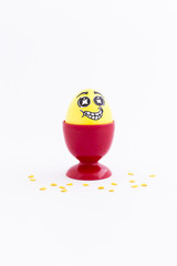 Yellow painted Easter egg with funny cartoon style face in a red plastic egg cup and yellow confetti on white background