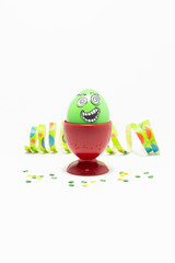 Green painted Easter egg with funny cartoon style face in a red plastic egg cup, colorful paper streamer and confetti on white background
