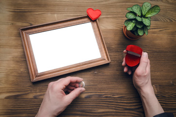 Photo frame with copy space in male hands and wedding ring in a present box. Declaration of love. Offer to get married. Miss of girl friend.
