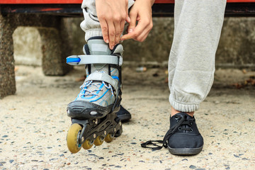 Woman putting on roller skates outdoor.