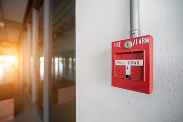 Red fire alarm mounted on the crack wall