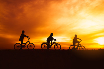 silhouette boys riding bicycle at sunset or sunrise background