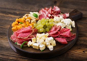 Aluminium Prints Appetizer Antipasto catering platter with bacon, jerky, sausage, blue cheese and grapes on a wooden background.