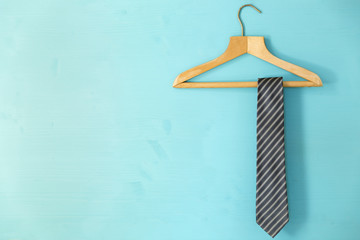 Male tie hanging on the rack, blue background. Father's day concept Fotobehang