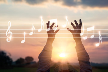 Abstract woman hands touching music notes on sunset nature background, music concept