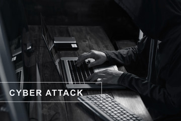 Internet crime. Hacker using laptop and hacking code password in dark room. Cyber attack concept