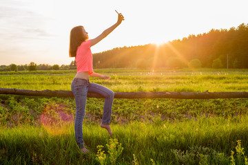 Teen girl doing selfie on phone on sunset background.