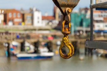 A rusty crane hook with blurry background of Bridlington harbour, East Riding of Yorkshire, UK
