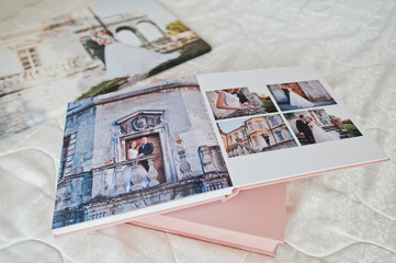 Pages with wedding photos of a photobook or photo album on bed.