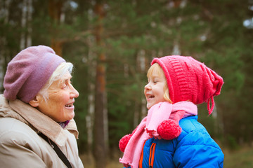 happy grandmother and granddaughter talk in nature