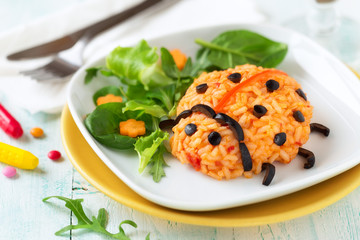 Ladybug risotto for kids - rice with tomatoes and olives served with fresh lettuce and arugula. Healthy fun food for kids