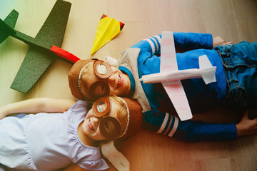 happy kids with helmet and glasses play with toy plane