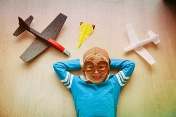happy little boy with helmet and glasses play with toy plane