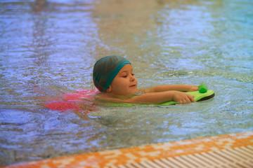 little girl learn to swim in swimming pool