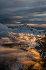 Dramatic Aerial view of a famous volcano that can be seen from Seattle and Vancouver, during a cloudy sunset. Located in Washington State, North America.