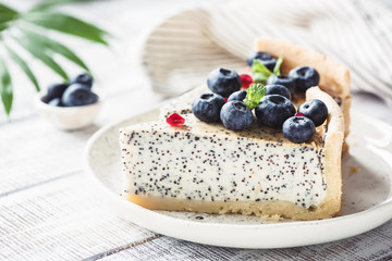 Cheesecake with poppy and blueberries on white plate. Closeup view, toned image