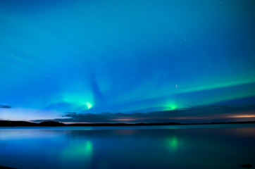 Northern lightd dancing over calm lake in Farnebofjarden national park in Sweden.