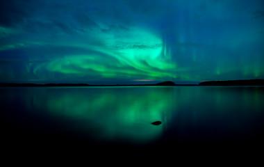 Northern lightd dancing over calm lake in Farnebofjarden national park in Sweden.