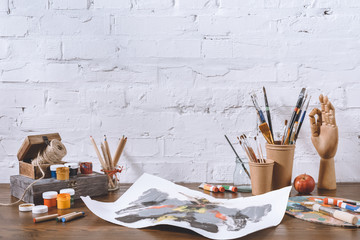 sketch and cups with brushes on wooden table in workshop