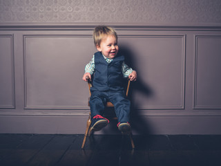 Smiling little boy sitting on a chair