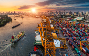 Logistics and transportation of Container Cargo ship and Cargo plane with working crane bridge in shipyard at sunrise, logistic import export and transport industry background Fototapete
