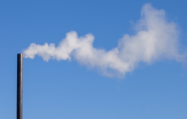 smoke from an industrial pipe on a background of blue sky
