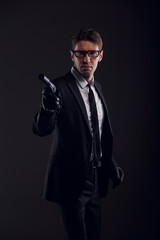 Picture of gangster man wearing glasses and leather gloves with gun