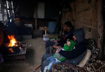 Palestinians warm themselves by a fire inside their house on a rainy day in Al-Shati refugee camp in Gaza City