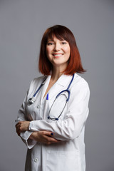 Photo of smiling female doctor in white lab coat and with phonendoscope