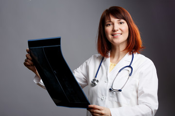 Photo of brunette doctor and white lab coat with X-ray