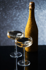 Festive picture of bottle of champagne in gold wrapper with two wine glasses