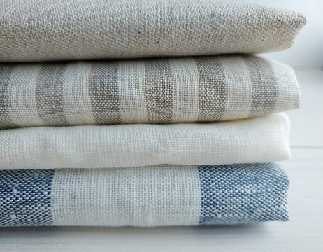 Pile of striped white grey blue red linen cotton fabrics on white background. Different colours. Food photo props. Natural linen cotton fabric.