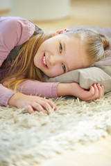 Mädchen liegt zur Entspannung auf Kissen