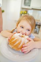 Kind beim Essen von Napfkuchen in Küche