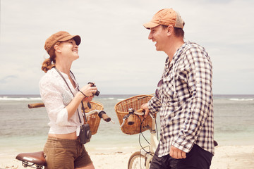 Cheerful young people talking and smile while standing near their old fashioned bicycles on beach.