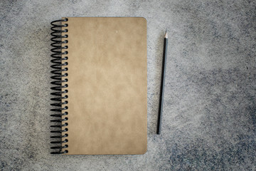 Spiral light brown cover bound notebook with pencil on grey background