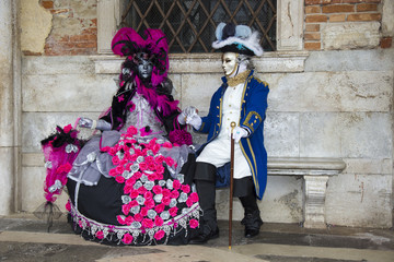 Venice Carnival - Lovely Couple of Venetian masks in colorful and elegant costume on St. Mark's Square in Venice.