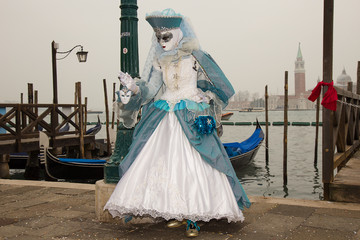Venice Carnival - Female Venetian Mask in blue costume with venetian gondolas -