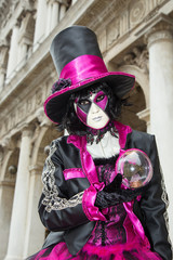 Venice Carnival - Female Venetian Mask with Magic Ball in pink / black elegant costume on St. Mark's Square in Venice with traditional venetian architecture in the background.
