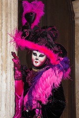 Cat mask - Female Venetian Mask in pink / black elegant costume on St. Mark's Square in Venice with traditional venetian pillar - Venice Carnival