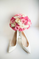 White shoes for a bride stand before pink wedding bouquet