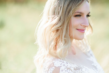 Stunning bride with white curls stands on the field in a sunny day