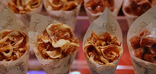 Spanischer Schinken als Snack in einer Reihe mit kleinen Portionstütchen