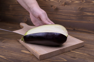 cutting the eggplant on a wooden board
